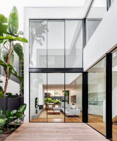 The internal courtyard looks into the living, dining and kitchen space of the home's groun ...