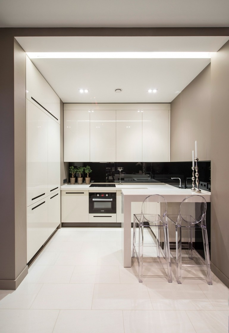Tiny Small Compact white kitchen with floor to ceiling cupboards and black splashback.