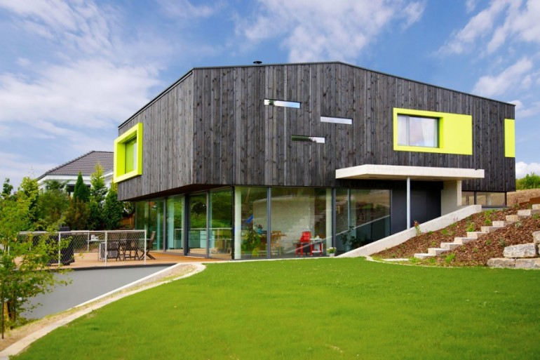 This German Family House is a Black Cuboid Supported by Glass Walls