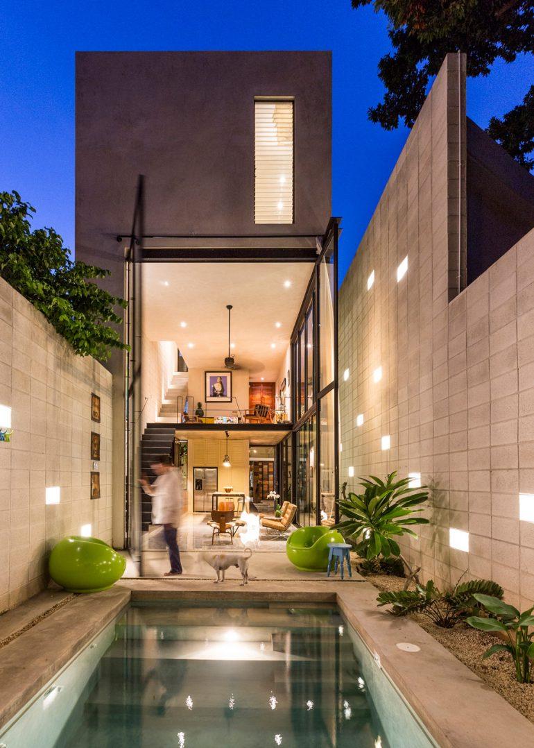 Huge glass doors open Mexican house to a courtyard garden